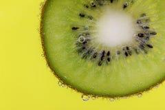 Le plan rapproché d'une tranche de kiwi couverte dans l'eau bouillonne sur un fond jaune Images libres de droits