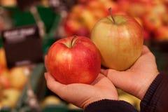 Le plan rapproché de cueillent à la main la pomme rouge et verte dans le supermarché photo libre de droits