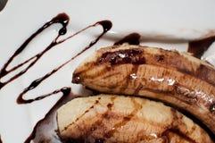 Le plan rapproché de deux bananes a fondu avec du chocolat Images stock