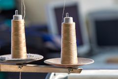 Le plan rapproché de deux bobines avec le beige filète sur une machine à coudre plus de Image stock