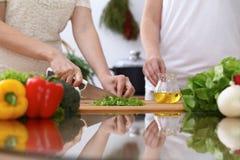 Le plan rapproché de deux femmes font cuire dans une cuisine Amis ayant l'amusement tout en préparant la salade fraîche Image stock