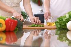 Le plan rapproché de deux femmes font cuire dans une cuisine Amis ayant l'amusement tout en préparant la salade fraîche Photos stock
