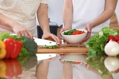 Le plan rapproché de deux femmes font cuire dans une cuisine Amis ayant l'amusement tout en préparant la salade fraîche Images stock