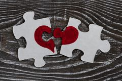 Le plan rapproché de deux a séparé les morceaux d'un puzzle qui forment ensemble un coeur sur une surface en bois rustique Photos libres de droits
