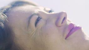 Le plan rapproché de femme regardant le ciel rêvant, rêveur menteur, femelle de sourire apprécie banque de vidéos