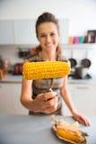 Le plan rapproché de l'épi de maïs s'est tenu par la main de la femme anonyme Photo libre de droits
