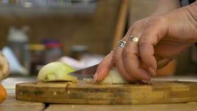 Le plan rapproché de l'épouse supérieure de maison remet couper un oignon préparant le dîner pour la famille banque de vidéos