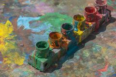 Le plan rapproché de l'artiste peint des pots sur un fond de palette Concept de bannière d'art image stock