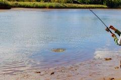 Le plan rapproché de l'des garçons remettent tenir la canne à pêche et la bobine Image stock