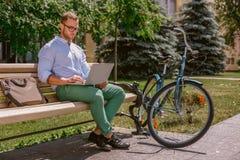 Le plan rapproché de l'homme d'affaires remet la dactylographie sur l'ordinateur portable tandis que des pauses-café en parc Photos stock