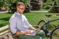 Le plan rapproché de l'homme d'affaires remet la dactylographie sur l'ordinateur portable tandis que des pauses-café en parc Photographie stock libre de droits