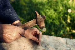 Le plan rapproché de l'homme mûr remet des clous avec le vieux marteau Image stock