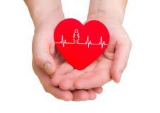 Le plan rapproché de l'homme remet tenir le coeur rouge avec la ligne d'ecg Photographie stock libre de droits