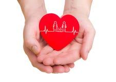 Le plan rapproché de l'homme remet tenir le coeur rouge avec la ligne d'ecg Photo libre de droits