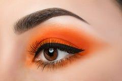 Le plan rapproché de l'oeil de femme avec le beau smokey orange observe photographie stock