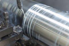 Le plan rapproché de la coupe de machine de tour l'axe en acier avec le fluide de liquide réfrigérant photo stock