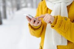 Le plan rapproché de la femme de mains à l'aide du smartphone mobile s'est relié au Image stock