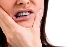 Le plan rapproché de la femme en douleur forte de mal de dents avec remet le visage photo stock