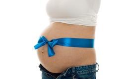 Le plan rapproché de la femme enceinte avec le grand ventre et la bande bleue là-dessus a isolé sur le fond blanc Photo libre de droits