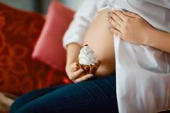 Le plan rapproché de la femme heureuse enceinte méconnaissable avec remet le ventre avec un gâteau blanc doux, un dessert et une  Image libre de droits