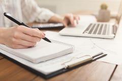 Le plan rapproché de la femme remet la dactylographie sur l'ordinateur portable et le compte sur la calculatrice Photo libre de droits