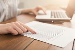 Le plan rapproché de la femme remet la dactylographie sur l'ordinateur portable et vérifier des papiers Photos libres de droits