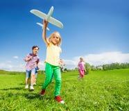 Le plan rapproché de la fille avec des enfants et l'avion blanc jouent Image stock