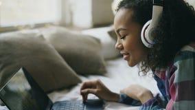 Le plan rapproché de la fille d'afro-américain écoutent la musique tout en observant des photos en ligne sur l'ordinateur portabl banque de vidéos