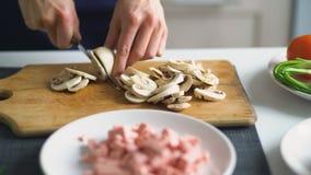 Le plan rapproché de la fille remet couper les champignons sur le conseil en bois pour la pizza dans la cuisine à la maison Photo libre de droits