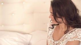 Le plan rapproché de la jeune femme attirante se réveillant en tant que son mari lui apporte le café dans le lit banque de vidéos