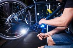 Le plan rapproché de la mécanique de bicyclette de mains du ` s de l'homme dans la boutique emploie l'instment pour ajuster et ré photographie stock libre de droits