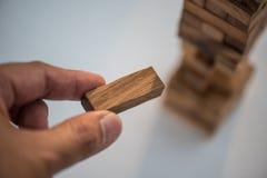 Le plan rapproché de la main asiatique du ` s de femme jouant les blocs en bois empilent le jeu Image stock