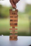 Le plan rapproché de la main asiatique du ` s de femme jouant les blocs en bois empilent le jeu Image libre de droits