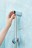 Le plan rapproché de la main de dépanneur ferme le support de douche de parenthèse de couverture Photo stock