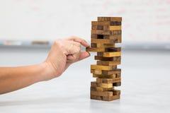 Le plan rapproché de la main jouant les blocs en bois empilent le jeu Photo stock