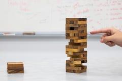 Le plan rapproché de la main jouant les blocs en bois empilent le jeu Image libre de droits