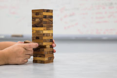 Le plan rapproché de la main jouant les blocs en bois empilent le jeu Photographie stock