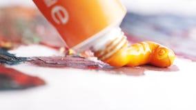Le plan rapproché de la peinture d'huile d'oranges a pressé du petit tube sur la toile peinte action Arts et concepts de peinture banque de vidéos