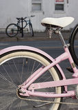 Le plan rapproché de la roue et le Seat d'un rose ont encadré la bicyclette garée et verrouillée sur la rue Une bicyclette bleue  Photos stock