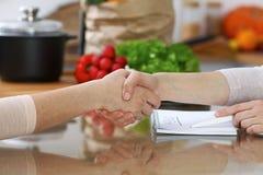 Le plan rapproché de la secousse remet une table dans la cuisine Amis ayant l'amusement tout en choisissant le menu pour la cuiss Photos libres de droits