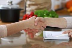 Le plan rapproché de la secousse remet une table dans la cuisine Amis ayant l'amusement tout en choisissant le menu pour la cuiss Photo libre de droits