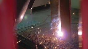 Le plan rapproché de la soudure d'électrode de deux pièces en métal est sur la table de soudure ?tincelles et flammes banque de vidéos