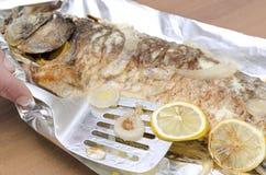 Le plan rapproché de la spatule, tranches de citron sur les poissons grillés de carpe a brûlé à des chips image libre de droits