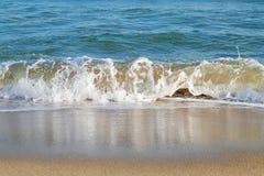 Le plan rapproché de la vague de mer avec la mousse blanche vient à terre La vague de mer est reflétée dans le sable côtier humid images libres de droits