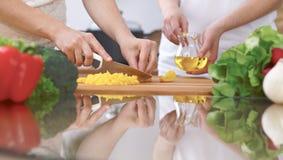 Le plan rapproché de quatre mains humaines font cuire dans une cuisine Amis ayant l'amusement tout en préparant la salade fraîche Photographie stock libre de droits
