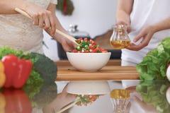 Le plan rapproché de quatre mains humaines font cuire dans une cuisine Amis ayant l'amusement tout en préparant la salade fraîche Photos libres de droits
