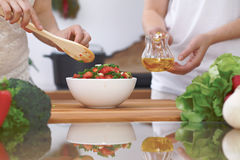 Le plan rapproché de quatre mains humaines font cuire dans une cuisine Amis ayant l'amusement tout en préparant la salade fraîche Image libre de droits
