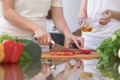 Le plan rapproché de quatre mains humaines font cuire dans une cuisine Amis ayant l'amusement tout en préparant la salade fraîche Photo stock