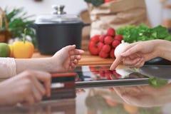 Le plan rapproché de quatre mains humaines sont gesticulent au-dessus d'un comprimé dans la cuisine Amis ayant l'amusement tout e Image libre de droits