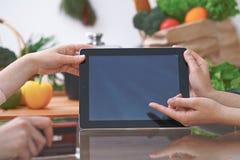 Le plan rapproché de quatre mains humaines sont gesticulent au-dessus d'un comprimé dans la cuisine Amis ayant l'amusement tout e Images stock